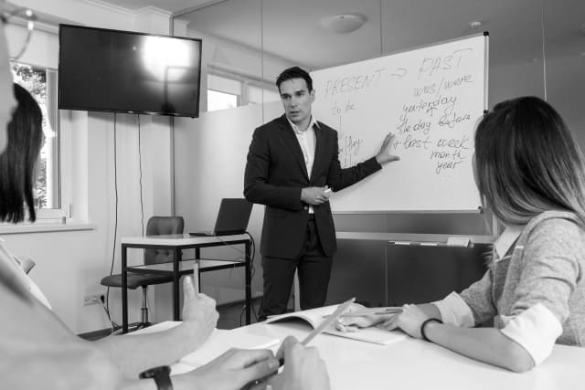 外国人の教師と生徒のモノクロ写真